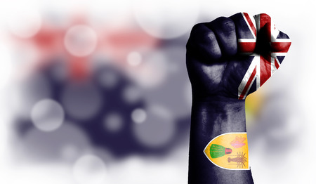 Flag of Turks and Caicos Islands painted on male fist, strength,power,concept of conflict. On a blurred background with a good place for your text.