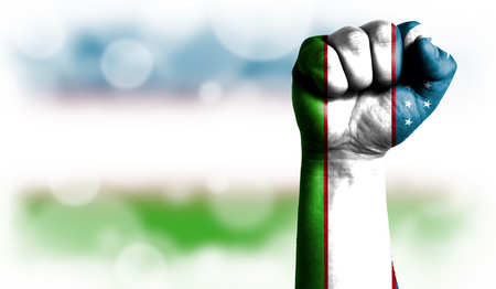 Flag of Uzbekistan painted on male fist, strength,power,concept of conflict. On a blurred background with a good place for your text.