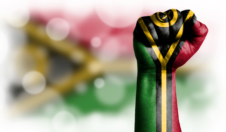 Flag of Vanuatu painted on male fist, strength,power,concept of conflict. On a blurred background with a good place for your text.