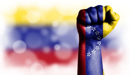 Flag of Venezuela painted on male fist, strength,power,concept of conflict. On a blurred background with a good place for your text. Stock Photo