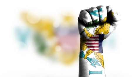 Flag of Virgin Islands of the United States painted on male fist, strength,power,concept of conflict. On a blurred background with a good place for your text.