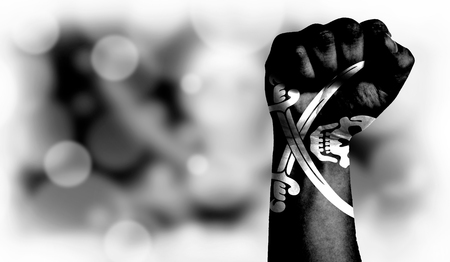 Flag of Pirates black painted on male fist, strength,power,concept of conflict. On a blurred background with a good place for your text.