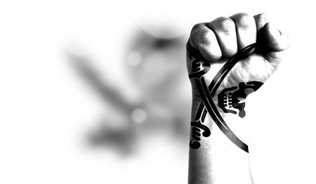 Flag of Pirates white painted on male fist, strength,power,concept of conflict. On a blurred background with a good place for your text.