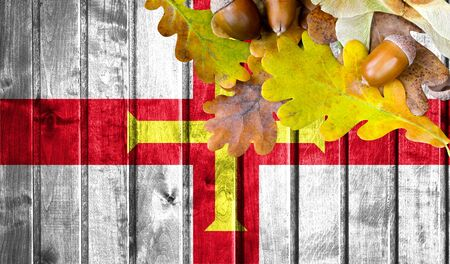 Madagascar flag on autumn wooden background with leaves and good place for your text.