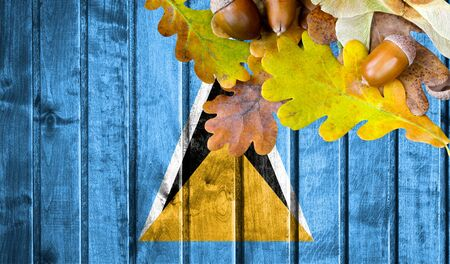Saint Lucia flag on autumn wooden background with leaves and good place for your text. Stock Photo
