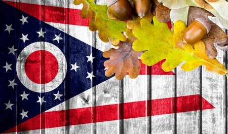 State of Ohio flag on autumn wooden background with leaves and good place for your text. Stock Photo