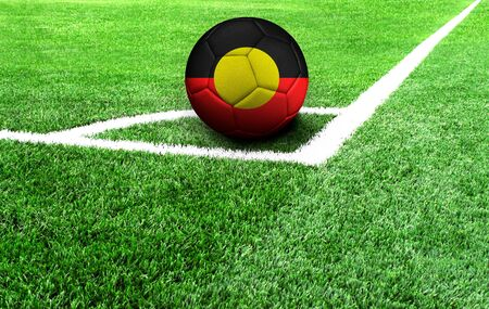 soccer ball on a green field, flag of Australian Aboriginal