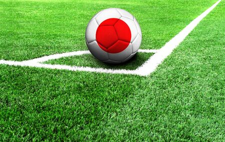 soccer ball on a green field, flag of Japan Stockfoto