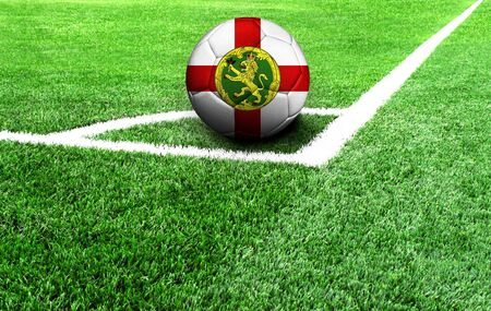 soccer ball on a green field, flag of Alderney