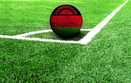 soccer ball on a green field, flag of Malawi Stockfoto