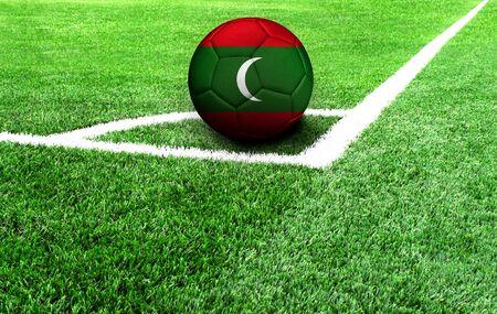 soccer ball on a green field, flag of Maldives Stockfoto