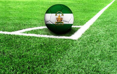 soccer ball on a green field, flag of Andalusia