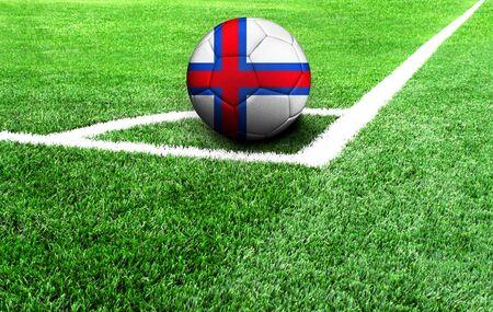 soccer ball on a green field, flag of Faroe Islands Stockfoto