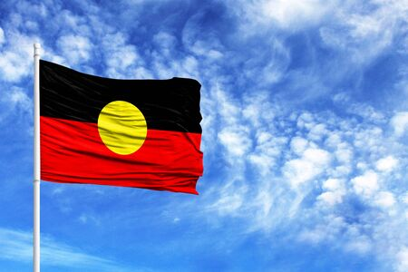 National flag of Australian Aboriginal on a flagpole in front of blue sky