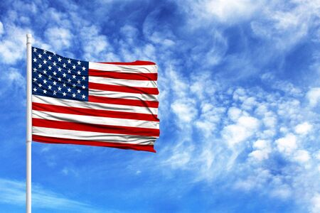 National flag of America on a flagpole in front of blue sky