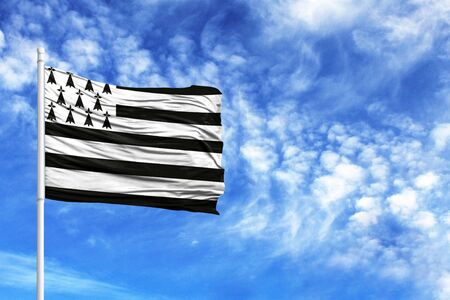 National flag of Brittany on a flagpole in front of blue sky