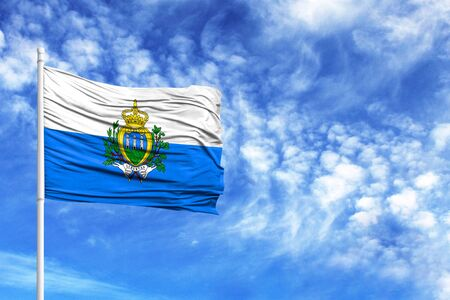 National flag of San marino on a flagpole in front of blue sky