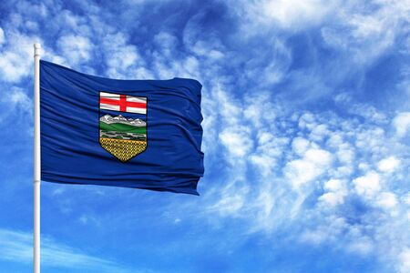 National flag of Alberta on a flagpole in front of blue sky