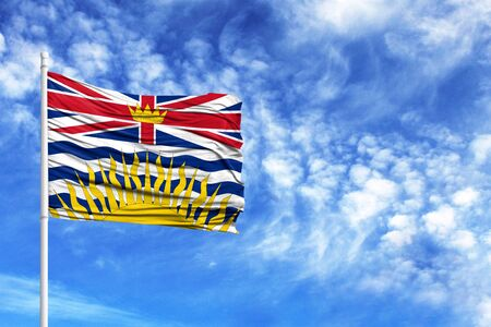 National flag of British Columbia on a flagpole in front of blue sky