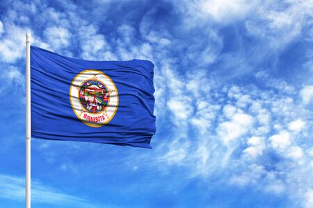 National flag State of Minnesota on a flagpole in front of blue sky Stock Photo