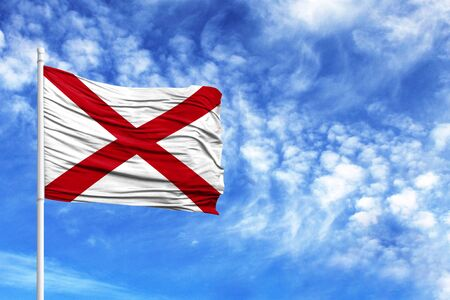 National flag State of Alabama on a flagpole in front of blue sky