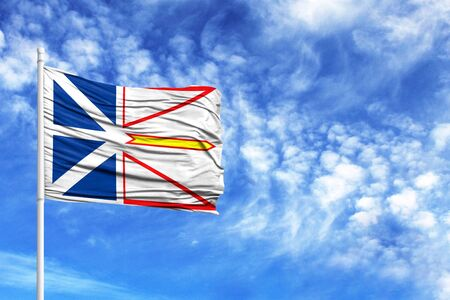 National flag of Newfoundland and Labrador on a flagpole in front of blue sky
