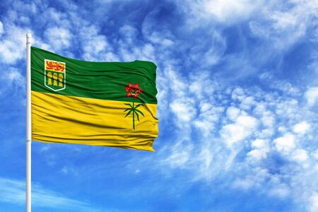 National flag of Saskatchewan on a flagpole in front of blue sky