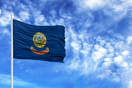 National flag State of Idaho on a flagpole in front of blue sky
