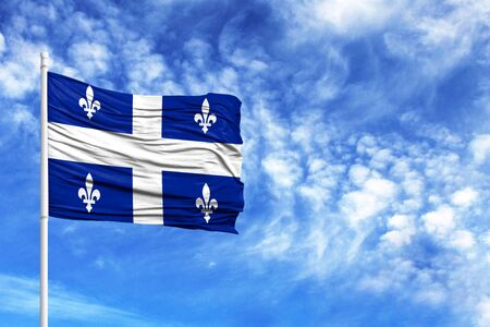 National flag of Quebec on a flagpole in front of blue sky