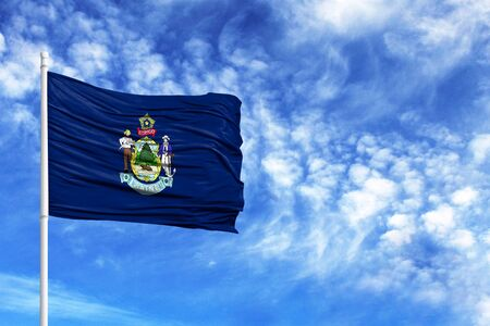 National flag State of Maine on a flagpole in front of blue sky Stock Photo