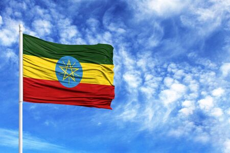National flag of Ethiopia on a flagpole in front of blue sky