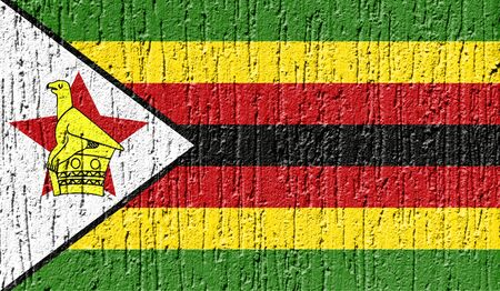 Flag of Zimbabwe close up painted on a cracked wall Фото со стока