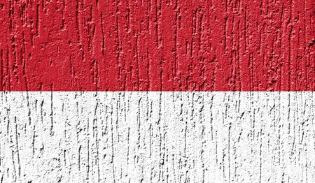Flag of Indonesia close up painted on a cracked wall Фото со стока