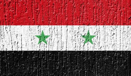 Flag of Syria close up painted on a cracked wall Фото со стока