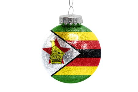 Glass Christmas ball toy isolated on white background with the flag of Zimbabwe