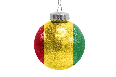 Glass Christmas ball toy isolated on white background with the flag of Guinea
