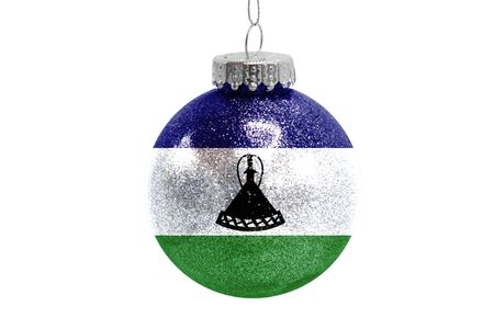 Glass Christmas ball toy isolated on white background with the flag of Lesotho Фото со стока