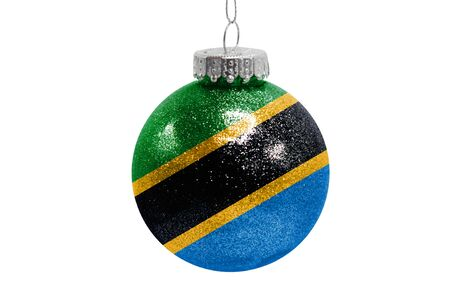 Glass Christmas ball toy isolated on white background with the flag of Tanzania
