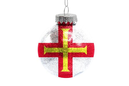 Glass Christmas ball toy isolated on white background with the flag of Guernsey