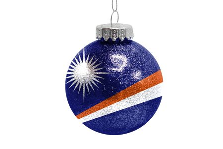 Glass Christmas ball toy isolated on white background with the flag of Marshall Islands