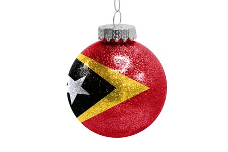 Glass Christmas ball toy isolated on white background with the flag of East Timor