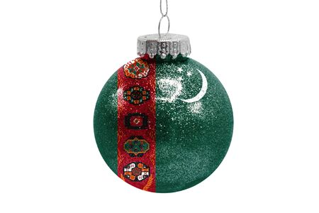 Glass Christmas ball toy isolated on white background with the flag of Turkmenistan Фото со стока