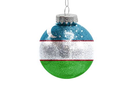 Glass Christmas ball toy isolated on white background with the flag of Uzbekistan