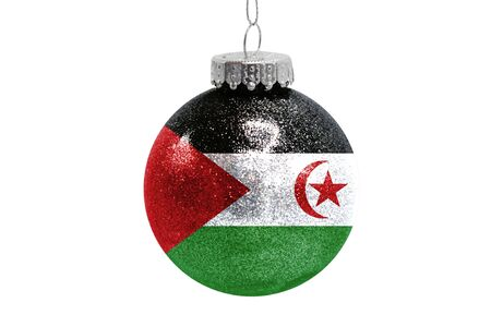 Glass Christmas ball toy isolated on white background with the flag of Western Sahara