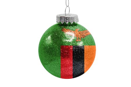Glass Christmas ball toy isolated on white background with the flag of Zambia