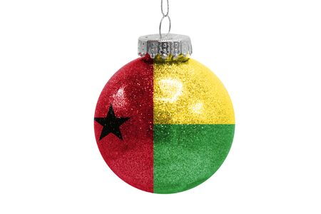 Glass Christmas ball toy isolated on white background with the flag of Guinea Bissau Фото со стока