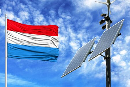 Solar panels on a background of blue sky with a flagpole and the flag of Luxembourg Stock Photo