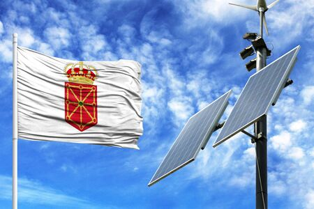 Solar panels on a background of blue sky with a flagpole and the flag of Navarra coat of arms Stock Photo