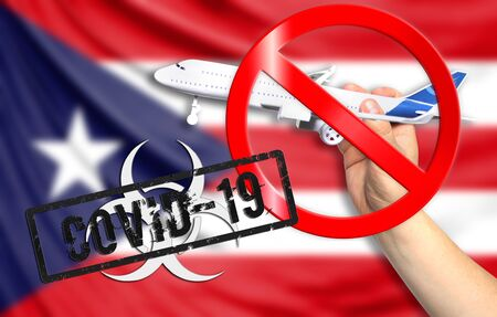 A new coronavirus disease called COVID - 19 with the flag of Puerto Rico. Contains the concept of a ban on air travel between countries. Фото со стока