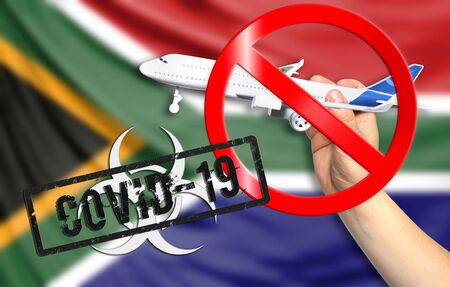 A new coronavirus disease called COVID - 19 with the flag of South Africa. Contains the concept of a ban on air travel between countries. Фото со стока